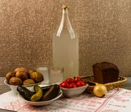 Ukrainian national drink and snack. The big bottle and glass of moonshine on the old wooden table. Russian vodka and snack. Royalty Free Stock Image