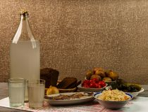 Ukrainian national drink and snack. The big bottle and glass of moonshine on the old wooden table. Russian vodka and snack. Royalty Free Stock Images