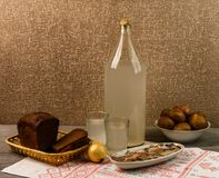 Ukrainian national drink and snack. The big bottle and glass of moonshine on the old wooden table. Russian vodka and snack. Stock Image