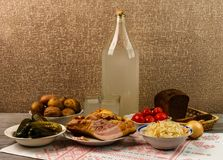 Ukrainian national drink and snack. The big bottle and glass of moonshine on the old wooden table. Russian vodka and snack. Stock Images
