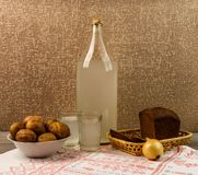 Ukrainian national drink and snack. The big bottle and glass of moonshine on the old wooden table. Russian vodka and snack. Stock Photography