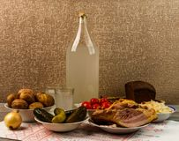 Ukrainian national drink and snack. The big bottle and glass of moonshine on the old wooden table. Russian vodka and snack. Stock Photos