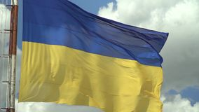 Ukrainian national flag against the sky. Ukrainian national flag against the blue sky slow motion stock video footage
