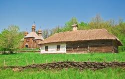 Ukrainian old log hut and church Stock Image