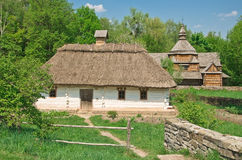 Ukrainian old log hut and church Stock Images