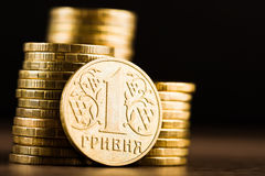 Ukrainian one hryvnia coin and gold money on the desk Stock Photos