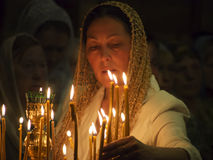 Ukrainian Orthodox celebrate Trinity. A woman lights a memorial candle --- Orthodox Christians around the world celebrate the day of the Holy Trinity. Trinity Stock Images