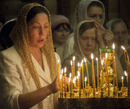 Ukrainian Orthodox celebrate Trinity. A woman lights a memorial candle --- Orthodox Christians around the world celebrate the day of the Holy Trinity. Trinity Stock Photo