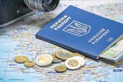 Ukrainian international biometric passport with dollars on a map background. Ukrainian passport with dollars on a map background. emigration kit for earnings or royalty free stock images