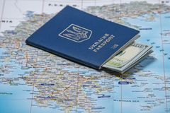 Ukrainian passport with dollars on a map background. Emigration kit for earnings or vacations stock photo