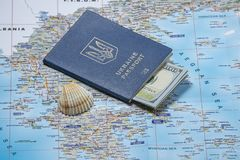 Ukrainian passport with dollars on a map background. Emigration kit for earnings or vacations royalty free stock photo
