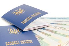 Ukrainian passports on a background of travel visas closeup. Two Ukrainian passports on a background of several travel visas closeup on a white background Royalty Free Stock Photos