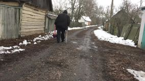 Ukrainian peasant with walking stick carrying string-bag moving on a winter street in Ukrainain village stock footage