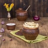 Ukrainian and Russian dishes - vareniki or dumplings with mashed potatoes or cottage cheese in clay pot on a wooden background. Close up Royalty Free Stock Image