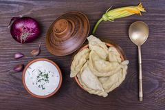 Ukrainian and Russian dishes - vareniki or dumplings with mashed potatoes or cottage cheese in clay pot on a wooden background. Close up Royalty Free Stock Photography