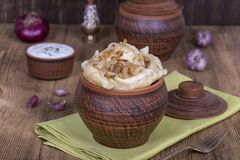 Ukrainian and Russian dishes - vareniki or dumplings with mashed potatoes or cottage cheese in clay pot on a wooden background. Close up Stock Photos