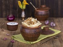 Ukrainian and Russian dishes - vareniki or dumplings with mashed potatoes or cottage cheese in clay pot on a wooden background. Close up Royalty Free Stock Photo