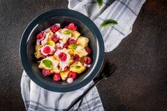 Ukrainian, Russian food, lazy vareniki; Curd or cheese gnocchi w. Ith fresh raw raspberries, cream and mint, on a dark concrete background, copy space top view royalty free stock photos