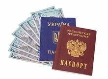 Ukrainian, Russian passports and  dollar bills Royalty Free Stock Photo