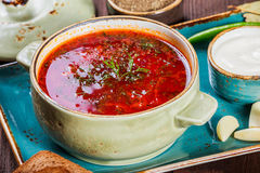 Ukrainian and Russian traditional beetroot soup - borscht in bowl with sour cream, garlic, herbs and bread on wooden background Stock Photos