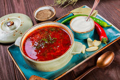 Ukrainian and Russian traditional beetroot soup - borscht in clay pot with sour cream, bread on dark wooden background. Ukrainian and Russian traditional Royalty Free Stock Photo