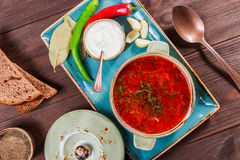 Ukrainian and Russian traditional beetroot soup - borscht in clay pot with sour cream, bread on dark wooden background. Ukrainian and Russian traditional Stock Image