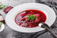 Ukrainian and Russian traditional beetroot soup - borscht in plate with spice, garlic, greens on rustic background, healthy food. Ingredients on table royalty free stock images
