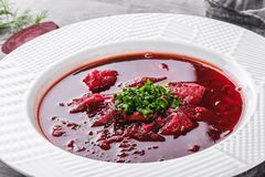 Ukrainian and Russian traditional beetroot soup - borscht in plate with spice, garlic, greens on rustic background, healthy food. Ingredients on table stock photography