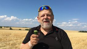 Senior farmer eating cucumber sitting outdoor against harvested wheat field and blue sky stock footage