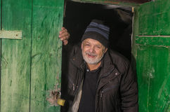 Ukrainian senior peasant looking out from barn Royalty Free Stock Photo