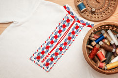 Ukrainian shirt with red-blue ornament. Ukrainian embroidery on a linen shirt, basket with threads and wattled cover with a thimble royalty free stock photo