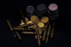 Ukrainian small coins with rifle military ammo on black background. Symbolizes war for money. Biggest problem in world stock photos