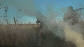 Ukrainian soldier aims, stand and walk on the field through the smoke. Front view stock footage