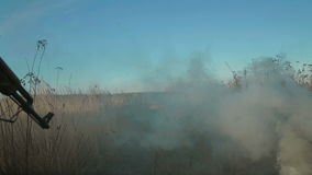 Ukrainian soldier aims and walk on the field through the smoke. Back view stock video