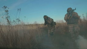 Ukrainian soldier aims and walk on the field through the smoke. Front view stock video footage
