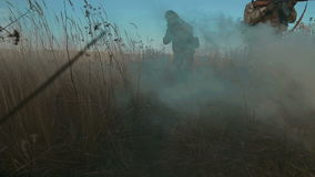 Ukrainian soldier aims and walk on the field through the smoke. stock video