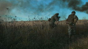 Ukrainian soldier aims and walk on the field through the smoke. Front view, move from left to right stock footage
