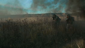 Ukrainian soldier aims and walk on the field through the smoke. Front view, move from right to left stock footage