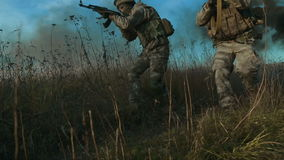 Ukrainian soldier aims and walk on the field through the smoke. Front view, move from right to left stock video footage
