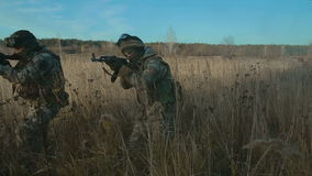 Ukrainian soldier aims and walk on the field through the smoke. Front view, move from right to left stock video