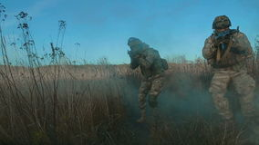 Ukrainian soldier aims and walk on the field through the smoke. stock footage