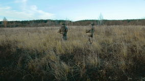 Ukrainian soldier run on the field. Back view stock video footage