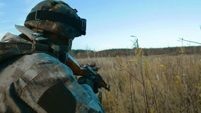 Ukrainian soldier takes aim. Back view. The goal is not visible stock footage