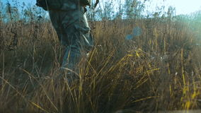 Ukrainian soldier walk on the field. It can be seen only the legs stock video footage
