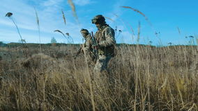 Ukrainian soldier walk on the field. Front view, move from left to right stock video