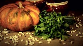 Ukrainian still life. The pumpkin. Ukrainian still life. The two ceramic pots, the big orange pumpkin, the parsley and strewed beans. Warm sacking background stock video footage