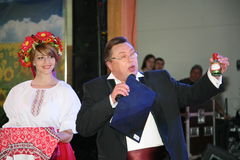 In the Ukrainian style. Beautiful girl actress animator in the national Ukrainian costume and Nikolay Y. Pozdeev - Entertainer. Performance in the restaurant of Stock Photo