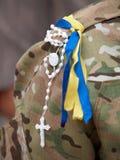 Ukrainian symbolics and the crucifix. Rosary with crucifix and ukrainian symbolics on a shoulder of volunteer Stock Photos