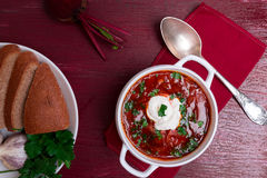 Ukrainian traditional borsch. Russian vegetarian red soup in white bowl on red wooden background. Top view. Borscht, borshch wit. H beet royalty free stock photography