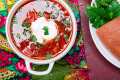 Ukrainian traditional borsch. Russian vegetarian red soup  in white bowl on red wooden background. Top view.  Borscht, borshch wit Stock Images